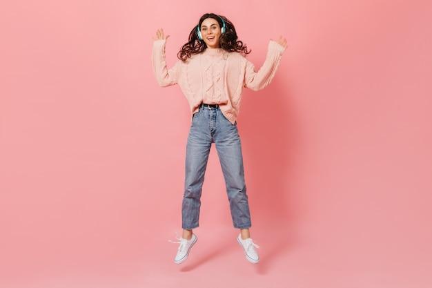 ピンクの背景にジャンプする陽気な女性の全身像。ヘッドフォンとニットのセーターを着たスタイリッシュな女の子が音楽を聴きます。