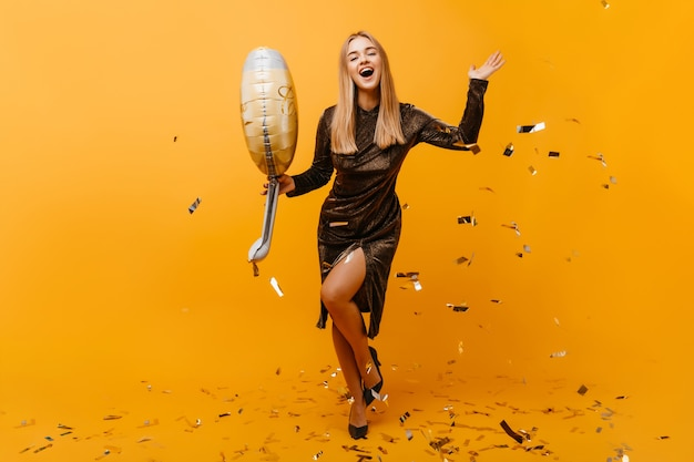 パーティーで踊るスパークルドレスを着た陽気な女性の全身像。オレンジ色に微笑んでいる魅力的な誕生日の女性。