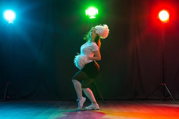 ポンポンと踊るチアリーダーの全身像。