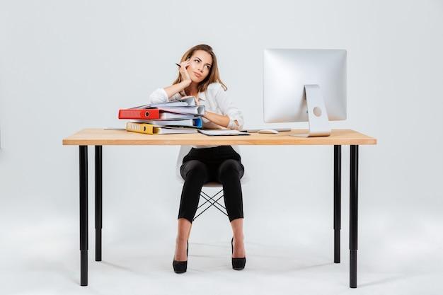 Полный портрет сосредоточенной задумчивой бизнес-леди, думающей о чем-то, держащем ручку, изолированную на белом фоне