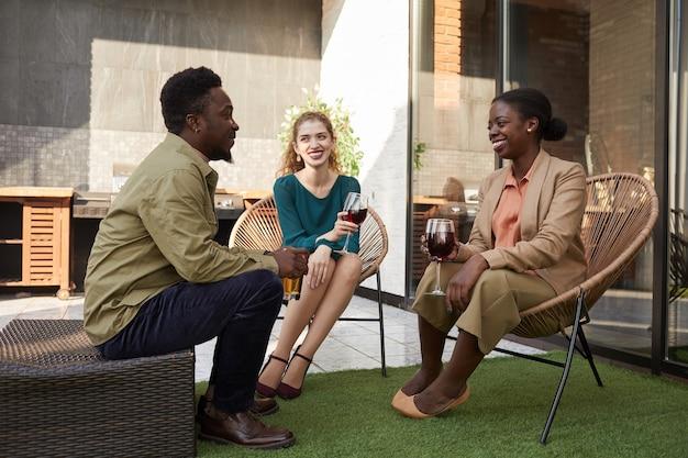 Портрет в полный рост современных взрослых людей, наслаждающихся беседой, сидя на плетеных стульях во время вечеринки на открытом воздухе