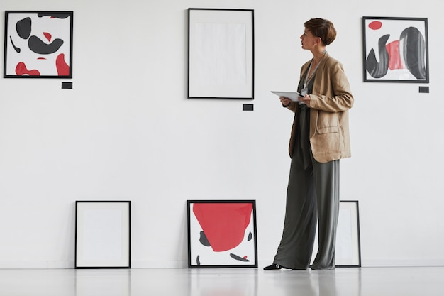 Портрет творческой элегантной женщины в полный рост, смотрящей на картины, висящие на белой стене, во время посещения выставки галереи современного искусства,