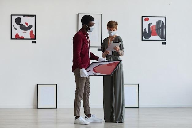 Портрет творческой татуированной женщины в полный рост, смотрящей на картины с афроамериканским мужчиной во время планирования выставки в галерее
