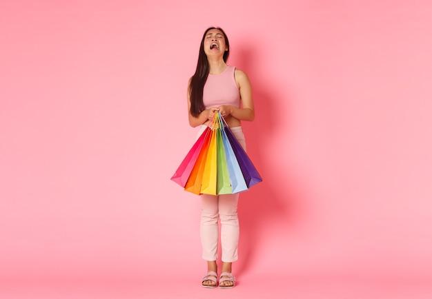 泣いてがっかりしている、お金が足りないと不平を言っているアジアの女の子が泣き叫んでいる、買い物袋を持っている、そしてすすり泣いている動揺の全身像、