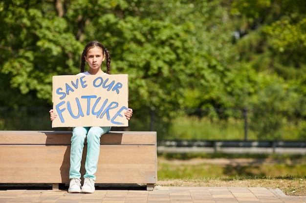 屋外で自然と経済に抗議しながらsavefutureの書き込みとサインを保持しているかわいい女の子の全身像、コピースペース