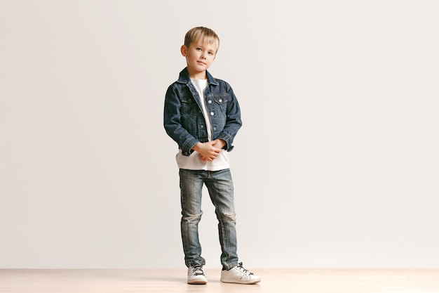 Полнометражный портрет милого маленького мальчика ребенка в стильной джинсовой одежде и усмехаясь, стоя на белизне. концепция детской моды