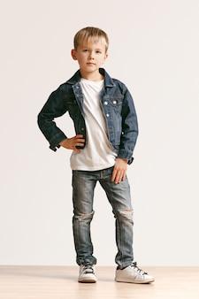 세련 된 청바지 옷을 입고 웃 고, 흰색에 서있는 귀여운 꼬마 소년의 전체 길이 초상화. 키즈 패션 컨셉