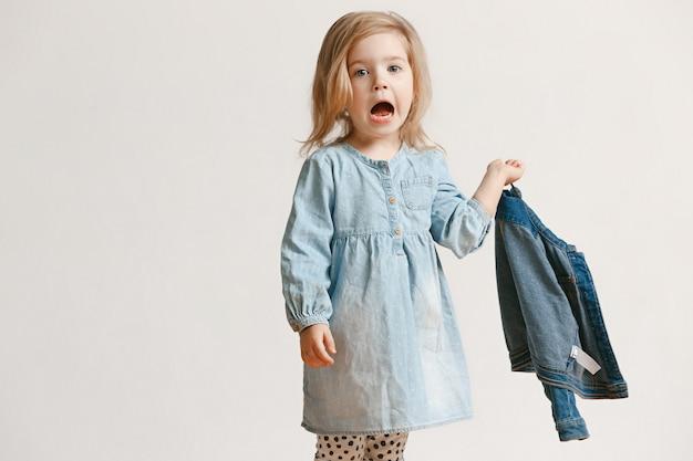 スタイリッシュなジーンズの服と笑顔、白の上に立っているかわいい小さな子供の女の子の全身像。キッズファッションコンセプト