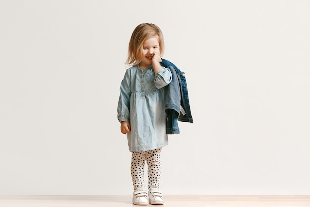 세련 된 청바지 옷을 입고 웃 고, 흰색에 서있는 귀여운 꼬마 소녀의 전체 길이 초상화. 키즈 패션 컨셉