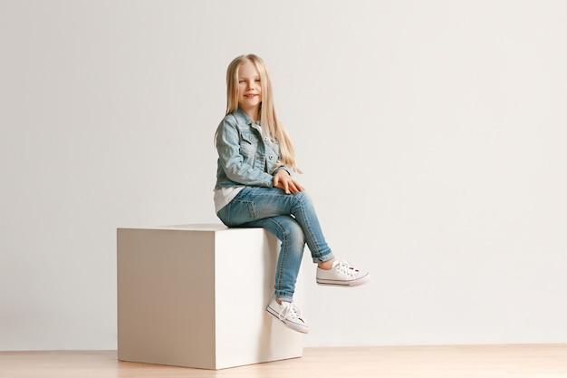 Полный портрет милой маленькой девочки в стильной джинсовой одежде и улыбки, стоя на белом. концепция детской моды