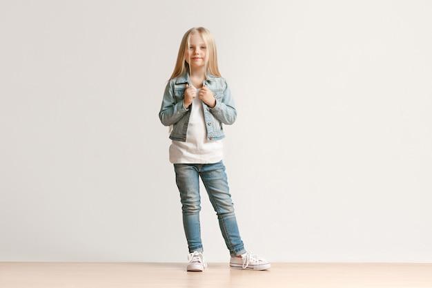 カメラを見て、白いスタジオの壁に立って笑っているスタイリッシュなジーンズの服を着たかわいい小さな子供の女の子の全身像。キッズファッションコンセプト