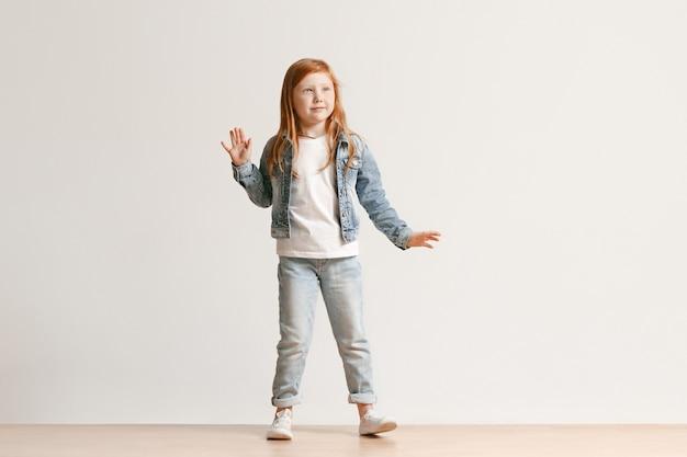 카메라를보고 웃 고, 흰색 스튜디오 벽에 서있는 세련 된 청바지 옷에 귀여운 꼬마 소녀의 전체 길이 초상화. 키즈 패션 컨셉