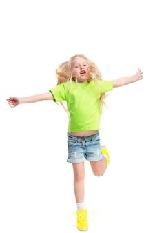 흰색 스튜디오 벽에 서서 카메라를 보고 웃고 있는 세련된 청바지 옷을 입은 귀여운 꼬마 소녀의 전체 길이 초상화. 키즈 패션 컨셉