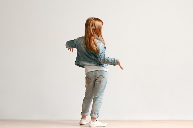 Полный портрет милой маленькой девочки в стильной джинсовой одежде, стоящей против белой стены студии. концепция детской моды