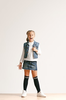 카메라를보고 흰색 스튜디오 벽에 웃 고 세련 된 청바지 옷에 귀여운 작은 십 대 소녀의 전체 길이 초상화. 키즈 패션 컨셉
