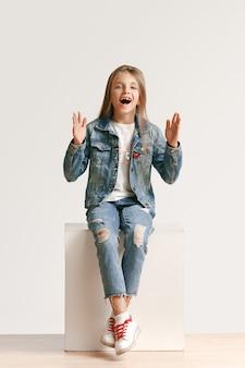 カメラ目線のスタイリッシュなジーンズ服でかわいい小さな十代の少女の完全な長さの肖像画