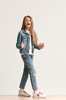カメラ目線と笑顔のスタイリッシュなジーンズ服でかわいい小さな10代の完全な長さの肖像画
