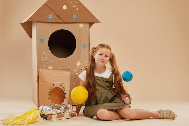 Портрет в полный рост симпатичной рыжеволосой девушки, играющей в космонавта, сидя на полу на картонной ракете