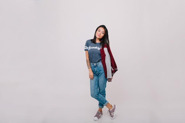 Портрет в полный рост темноволосой модели в джинсовых брюках. довольно брюнетка девушка в джинсах и модной футболке позирует