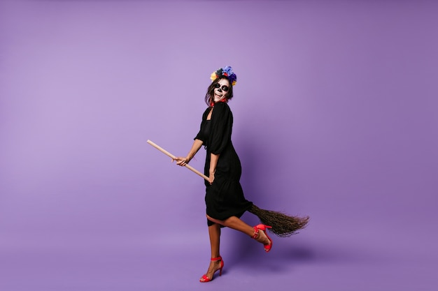 ハロウィーンで踊る死んだ花嫁の全身像。ほうきに座って興奮したブルネットの魔女。
