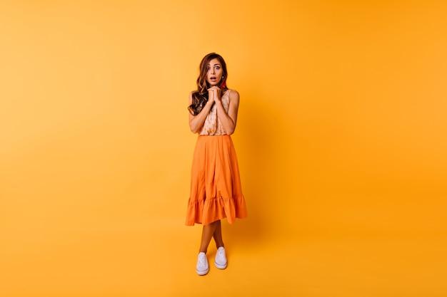 긴 치마에 debonair 생강 여자의 전신 초상화. 화려한 아가씨는 스튜디오에서 포즈를 취하는 주황색 옷을 입는다.