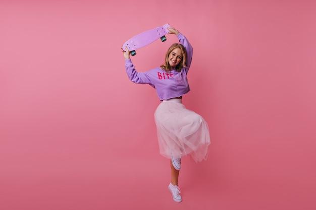 スケートボードで浮気しているデボネアの若い女性の全身像。パステルで踊るスリムでスタイリッシュな女の子の屋内の肖像画。
