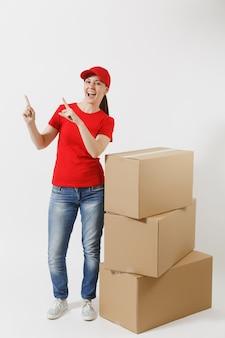 빨간 모자를 쓴 배달 여성의 전체 길이 초상화, 흰색 배경에 격리된 티셔츠. 빈 판지 상자 근처에 서 있는 여성 택배 또는 딜러. 패키지를 받고 있습니다. 광고 공간을 복사합니다. 프리미엄 사진