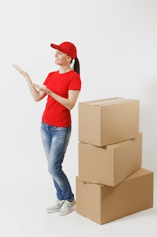 빨간 모자를 쓴 배달 여성의 전체 길이 초상화, 흰색 배경에 격리된 티셔츠. 빈 판지 상자 근처에 서 있는 여성 택배 또는 딜러. 패키지를 받고 있습니다. 광고 공간을 복사합니다.