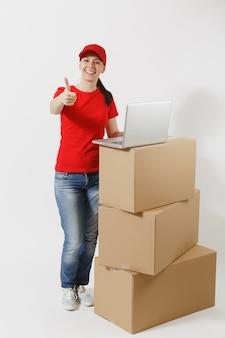흰색 배경에 격리된 빨간 모자를 쓴 배달 젊은 여성의 전체 길이 초상화. 노트북 pc 컴퓨터가 있는 빈 판지 상자 근처에 서 있는 여성 택배. 패키지를 받고 있습니다. 복사 공간