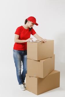 흰색 배경에 격리된 빨간 모자를 쓴 배달 젊은 여성의 전체 길이 초상화. 태블릿 pc 컴퓨터가 있는 빈 판지 상자 근처에 서 있는 여성 택배. 패키지를 받고 있습니다. 복사 공간