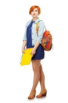 フォルダーとバックパックを備えた勤勉な女子学生の全身像色付きのバックパックを備えた大学または大学白で隔離