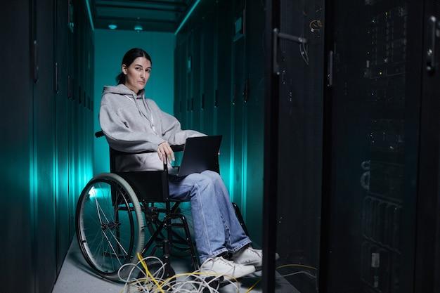 サーバールーム、アクセシブルな仕事の概念、コピースペースでラップトップを使用しながらカメラを見ている障害のある女性の完全な長さの肖像画