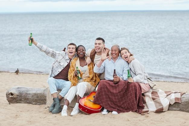 가을 해변에서 캠핑을 즐기고 사진을 위해 포즈를 취하는 다양한 친구들의 전체 길이 초상화