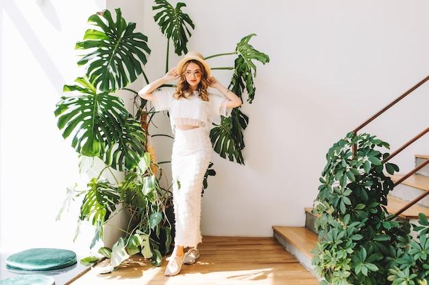 Портрет в полный рост мечтательной девушки в белых кроссовках и юбке, стоящей с поднятыми руками в тени большого зеленого цветка
