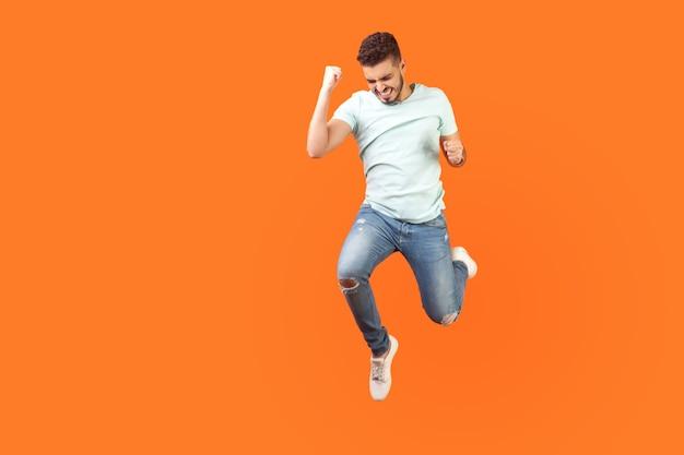 Полнометражный портрет восторженного брюнет с бородой в кроссовках и джинсовой одежде, прыгающий в воздухе, показывая, что да, я сделал это жестом, скопируйте место для рекламы. закрытый студийный выстрел изолирован на оранжевом фоне