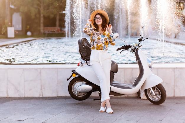 自転車に乗った後にポーズをとってメガネと夏の帽子のエレガントなブルネットの少女の全身像