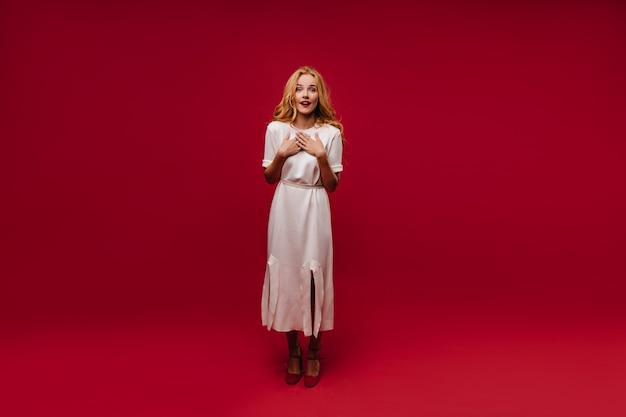 긴 가운에 우아한 백인 여자의 전신 초상화. 붉은 벽에 고립 된 감정적 인 곱슬 소녀입니다.