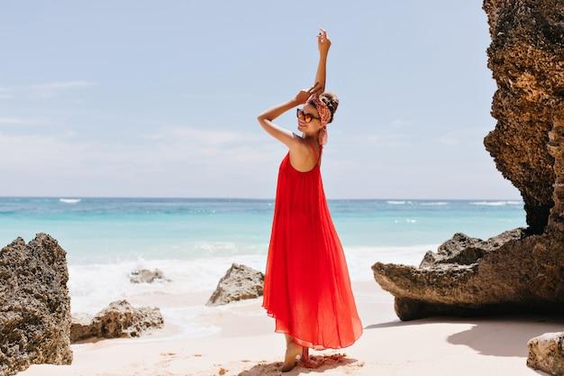 海の近くで笑っているエレガントなヨーロッパの女性の全身像。ビーチでポーズをとって赤で見事な日焼けした女の子