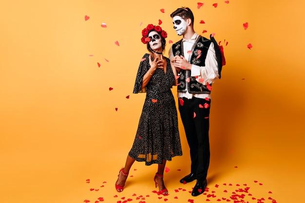 彼氏とハロウィーンでポーズをとるエレガントなラテンゾンビの女の子の全身像。