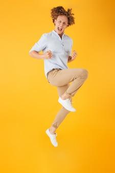 黄色の背景の上に分離された、拳をジャンプして握りしめるエネルギッシュな陽気な男の全身像