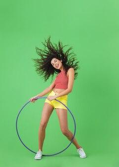 Полная длина портрет европейской женщины 20 лет в летней одежде, делающей упражнения с обручем во время гимнастики на зеленой стене