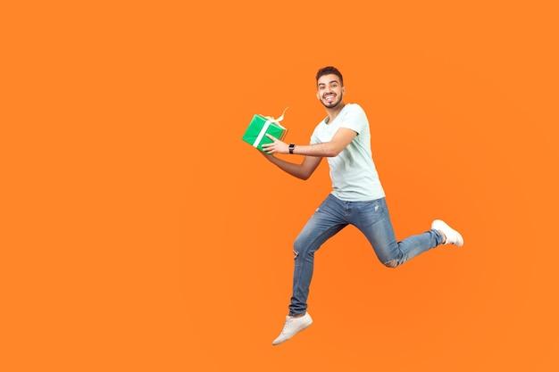 운동화와 데님 옷을 입은 흥분한 브루네트 남자의 전체 길이 초상화는 선물 상자를 들고 날아가거나 공중에서 달리면서 카메라를 향해 웃고 있습니다. 오렌지 배경에 고립 된 스튜디오 촬영