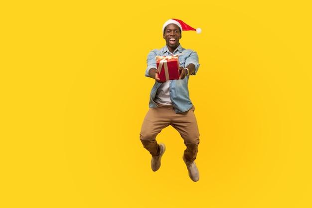 산타 모자와 캐주얼 데님 셔츠를 입은 매우 행복한 청년의 전체 길이 초상화는 점프하거나 날아가며 카메라에 크리스마스 선물 상자를 줍니다. 노란색 배경에 고립 된 실내 스튜디오 촬영