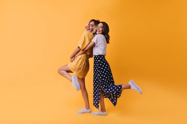 친구와 춤추는 롱 스커트에 매혹적인 소녀의 전신 초상화. 행복을 표현하는 세련된 옷을 입은 기쁜 여성 모델.
