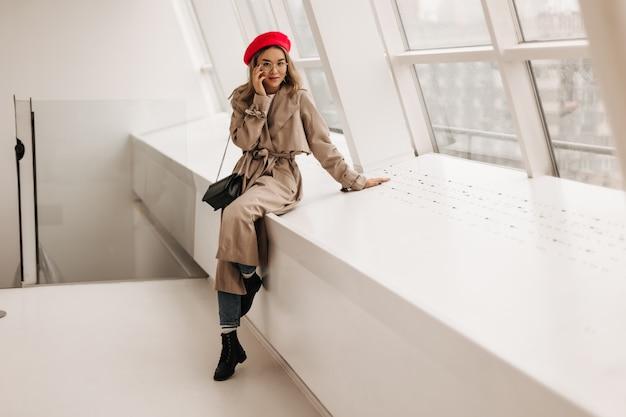 黒の靴、ジーンズ、ライトトレンチコートでファッショナブルなアジアの女性の全身像、黒いバッグと窓のそばでポーズ