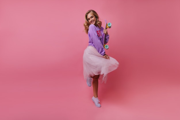 Полнометражный портрет модной дамы, стоящей на одной ноге и улыбающейся. стильная милая женщина с дурачиться скейтбордом.