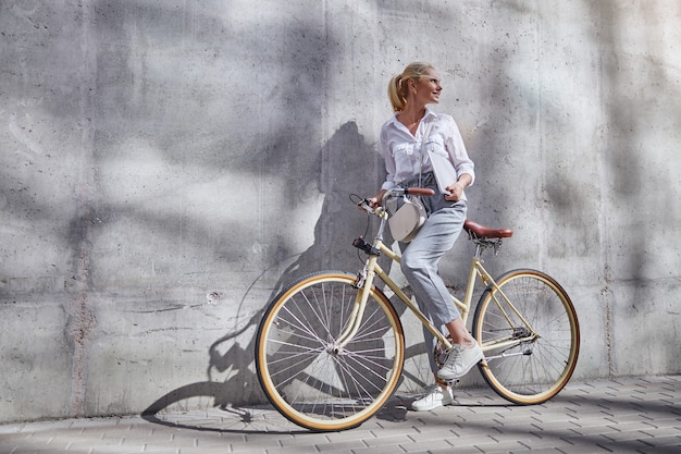 회색 벽에 격리된 도시 자전거 핸들에 손을 얹고 비즈니스 캐주얼 옷을 입은 세련된 여성의 전체 길이 초상화