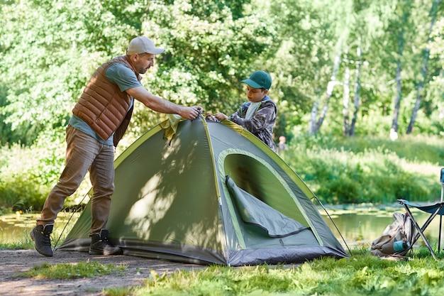 Портрет в полный рост отца и сына, устанавливающих палатку вместе, наслаждаясь кемпингом в лесу, копия пространства