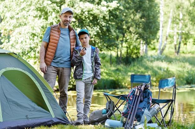Полнометражный портрет отца и сына, стоящих у палатки и наслаждающихся походом, копия пространства