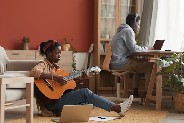 기타를 연주하고 녹음 스튜디오에서 바닥에 앉아있는 동안 노트북을 사용하는 여성 아프리카 계 미국인 음악가의 전체 길이 초상화, 복사 공간